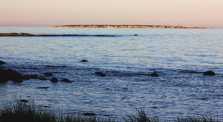 Foto taget från Gotlands kust ut över Östersjön i skymningsljus. Vid horisonten är Heligholmen med sin vita fyr fortfarande solbelyst mot en rosaskiftande himmel.